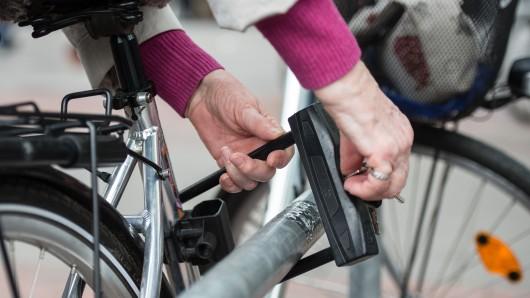 Eine Frau schließt in einer Fußgängerzone ein Fahrrad mit einem Fahrradschloss an einen Metallbügel an.