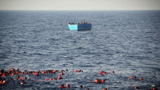 Flüchtlinge in Schwimmwesten treiben vor Libyen im Mittelmeer. Im Hintergrund schwimmt ein Boot, das mit Flüchtlingen besetzt ist (Symbolbild).