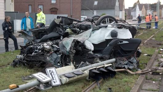 Ein völlig zerstörtes Auto liegt am 31. Mai 2017 auf den Schienen einer Straßenbahn in Braunschweig (Niedersachsen), nachdem es gegen einen Oberleitungsmast gefahren war. Nach Polizeiangaben raste ein Mann in der Nacht zu Mittwoch mit rund 200 Stundenkilometern durch die Innenstadt, nachdem er vor einer Polizeikontrolle auf der A2 geflüchtet war.