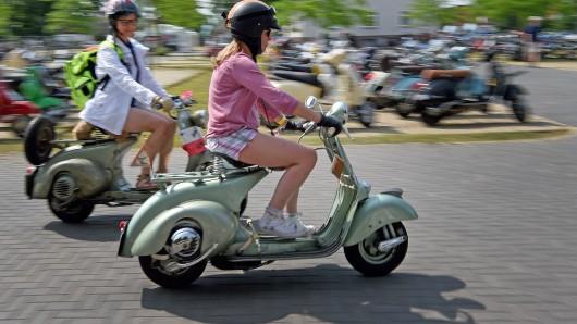 Zwei Vespa-Fahrerinnen vom Vespa Club Hamburg fahren auf das Veranstaltungsgelände des Vespa-Treffs.