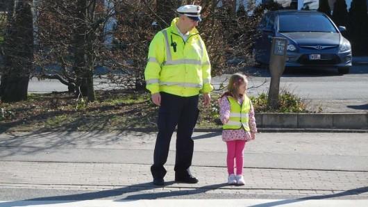 Kommissar Jens Oertelt übt mit der kleinen Julia das richtige Verhalten am Zebrastreifen.
