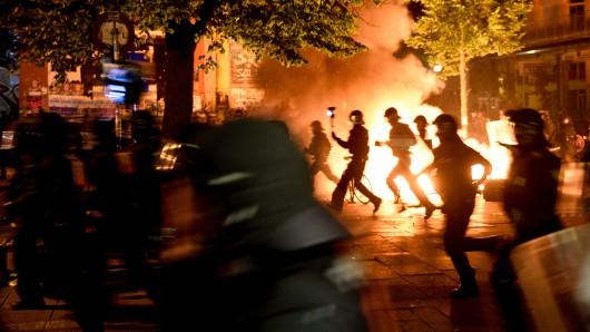 Polizisten laufen im Schanzenviertel an einer brennenden Barrikade vor der Roten Flora entlang.