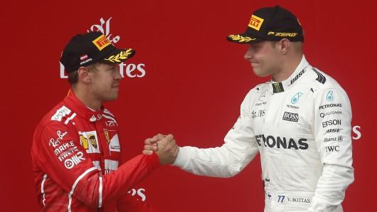 Sieger Valtteri Bottas (r.) aus Finnland vom Mercedes AMG Petronas F1 Team und der Zweitplatzierte Sebastian Vettel (l.) aus Deutschland von Scuderia Ferrari geben sich die Hand bei der Siegerehrung auf dem Podium.