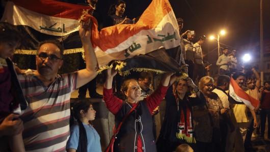 Die Menschen feiern am 9. Juli auf dem Tahrir-Platz in Bagdad (Irak), halten Nationalflaggen hoch und warten auf die Nachricht über die Niederlage der Terrormiliz Islamischer Staat in Mossul.