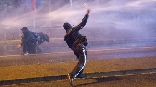 Ein Randalierer wirft am 9. Juli in Hamburg im Schanzenviertel eine Flasche in die Richtung eines Wasserwerfers.