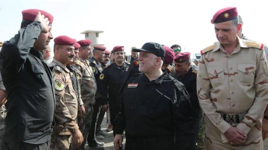 Der irakische Ministerpräsident Haider al-Abadi (2.v.l.) kommt am 9. Juli in Mossul (Irak) mit Polizisten und Armee-Offizieren an, um den Sicherheitskräften vor Ort zur Befreiung der Stadt und zum Sieg über die IS-Anhänger zu gratulieren.