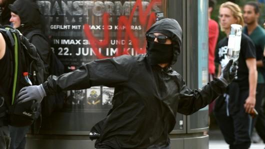 Ein maskierter Demonstrant wirft in Hamburg eine Flasche auf Polizeikräfte (Archivbild).