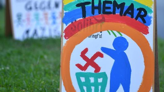 Eine Fahne mit der Aufschrift Refugees not welcome und andere Fahnen wehen in Themar (Thüringen) auf dem geplanten Veranstaltungsgelände für ein Rechtsrock-Konzert.