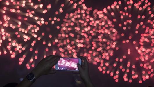 Feuer und bunte Lichter erhellen den Himmel über dem See. (Symbolbild)