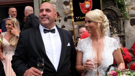 Er im Smoking mit Fliege, sie im weißen Kleid mit Mega-Ausschnitt: Rocker-Boss Frank Hanebuth und seine Frau Sarah nach der Trauung in der St.-Michaelis-Kirche in Bissendorf.