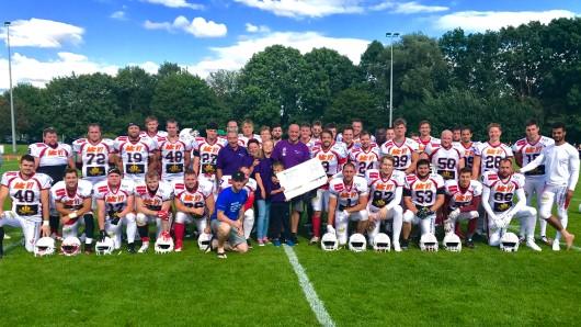Lila Hoffnung-Vorsitzender Holger Busse mit dem symbolischen Spendenscheck inmitten der Spieler der NewYorker Lions II.
