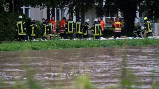 Feuerwehrleute räumen am 26.07.2017 am Ufer des Flusses Innerste in Hildesheim (Niedersachsen) Sandsäcke beiseite. Nach starken Regenfällen hat die Innerste in der Nacht am Pegel Heinde einen Rekordstand erreicht.