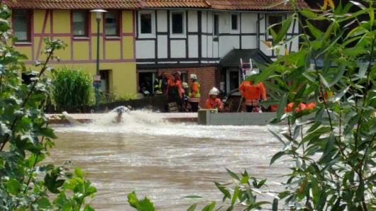 Einsatzkräfte der Feuerwehr kontrollieren von der Überflutung bedrohte Häuser: Muss hier jemand noch in Sicherheit gebracht werden?