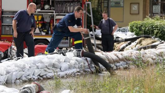 Einsatzkräfte der Freiwilligen Feuerwehr Wolfenbüttel verlegen weitere Schlauchleitungen, um die Fluten abzupumpen.