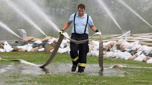 Ein Helfer trägt im Garten es Altenheims Steinhäuser Gärten einen Feuerwehrschlauch. Durch den Einsatz von