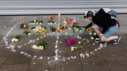 In einem aus Teelichtern gebildeten Peace-Zeichen legen Passanten zum Ausdruck ihrer Trauer Blumen nieder und entzünden Kerzen.