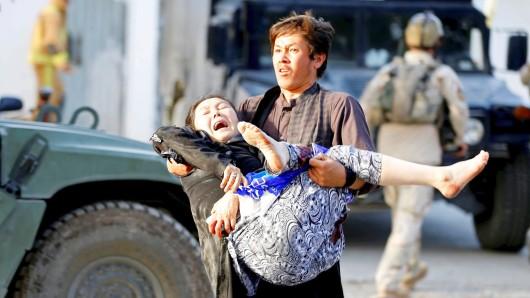 Ein Afghane trägt eine Verletzte nach dem Anschlag auf die vollbesetzte Moschee in Sicherheit.