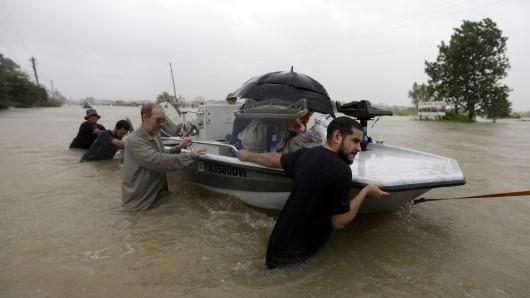 Menschen in Houston (Texas), in den völlig überfluteten Straßen der Stadt.