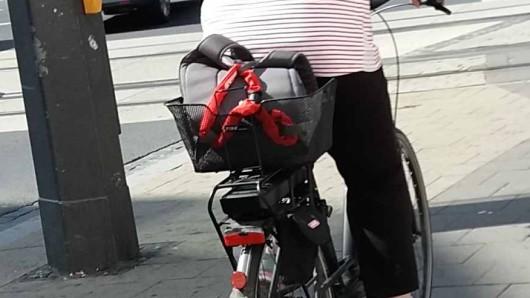 Ein Beispiel für einen gesicherten Fahrradkorb: Ein auffälliges, rotes Schloss umschließt die Henkel des Rucksacks.