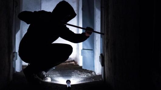Ein fiktiver Einbrecher hebelt eine Tür auf.