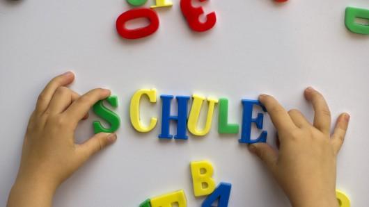 Ein Kind schreibt mit Magnetbuchstaben das Wort Schule an eine Magnettafel. Eine Untersuchung hat jetzt gezeigt, dass jedes fünfte Kind mit Sprachstörungen in die Schule kommt.