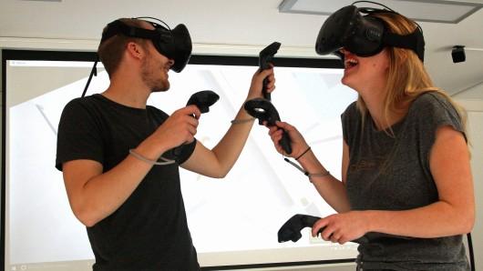Irina Shiyanov und Max Bäßmann vom Team der VirtuaLounge erkunden mit Hilfe von Virtual-Reality-Brillen ein Raumschiff.