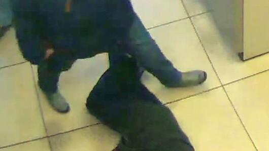 Auf diesem Überwachungsbild ist zu sehen, wie ein Bankkunde über den sterbenden Rentner hinwegsteigt, der im Vorraum eines Geldinstituts in Essen zusammengebrochen war.