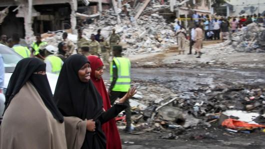 Somalische Frauen stehen einen Tag nach dem verheerenden Anschlag am völlig verwüsteten Tatort.