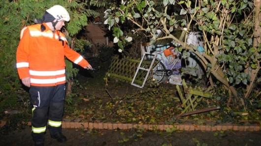 Ortsbrandmeister Jens Klages zeigt auf den vom 89-Jährigen Braunschweiger durchbrochenen Gartenzaun.