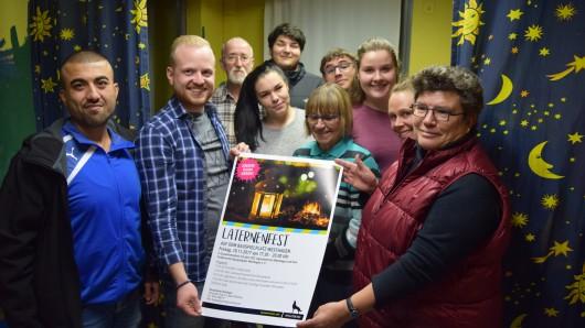 Mitarbeiter vom Bauspielplatz Westhagen sowie Ehrenamtliche des Fördervereins präsentieren das Plakat zum diesjährigen Laternenumzug.