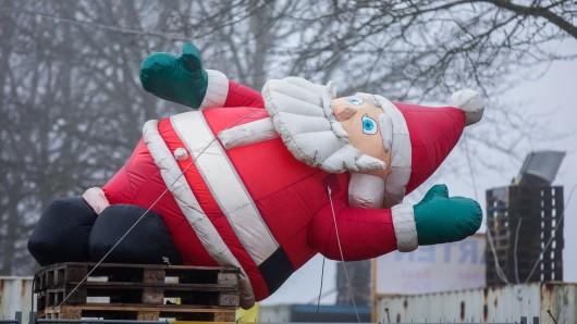 Ein aufblasbarer Weihnachtsmann liegt am 20. Dezember in der Nähe von Gadebusch (Mecklenburg-Vorpommern) vor einem Einkaufsmarkt auf einem Palettenstapel.