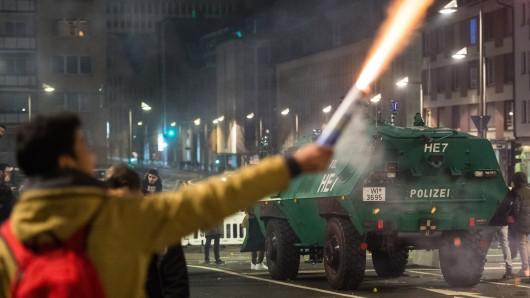 Ein Mann brennt in unmittelbarer Nähe eines gepanzerten Polizeifahrzeugs am 01.01.2018 in Frankfurt am Main (Hessen) Feuerwerk ab. In der Mainmetropole wurde für Silvester 2017/18 eine Sicherheitszone für bis zu 30.000 Besucher eingerichtet.