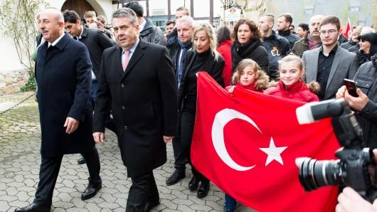 Begleitet von laut Polizei etwa 60 türkischstämmigen Demonstranten spazieren Bundesaußenminister Sigmar Gabriel (SPD) und sein türkischer Amtskollege Mevlüt Cavusoglu (l.) durch die Goslarer Innenstadt.