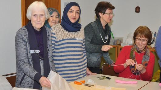 Renate Demski (von links) zeigt Rawaa Al Suwayyid, wie sie ihr Schnittmuster auf den Stoff überträgt. Beide kennen sich bereits aus Ampleben.
