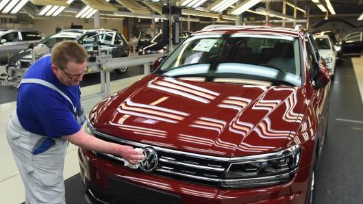 Ein Mitarbeiter reinigt in der Endabnahme im Volkswagen Werk in Wolfsburg einen VW Tiguan. (Archivbild)
