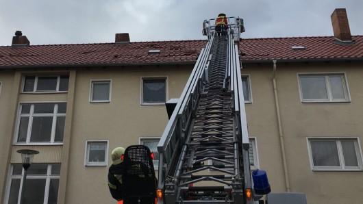 Mit Hilfe der Drehleiter sichern Einsatzkräfte der Wolfenbütteler Feuerwehr dieses von Friederike gefledderte Dach.