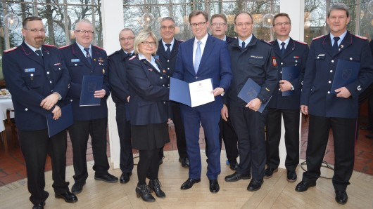 Mitglieder der Freiwilligen Feuerwehren aus dem Landkreis Gifhorn nehmen von Landrat Andreas Ebel (CDU, Mitte) die Dank-Urkunden entgegen.