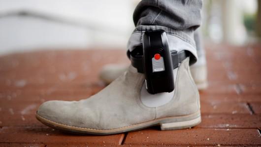 Am Bein eines Mannes ist eine elektronsche Fußfessel befestigt.