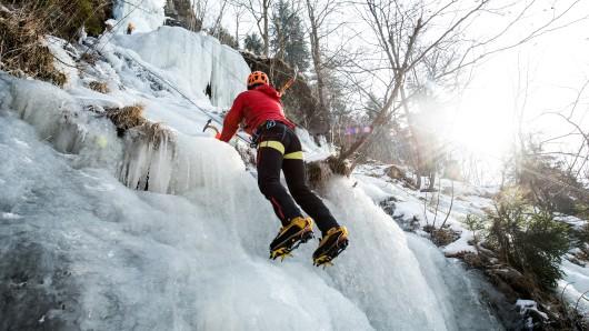 Ein Eiskletterer erklimmt den gefrorenen Romkerhaller Wasserfall.