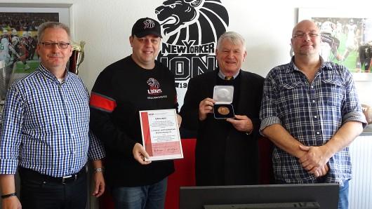 Von links: 1. Vorsitzender Andreas Rübeling, Head Coach Troy Tomlin, Prof. Dr. Arnd Krüger und der zweite Vorsitzende Marco Drescher.