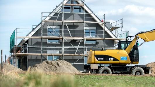 Ein eingerüsteter Rohbau eines Einfamilienhauses steht in einem Neubaugebiet in Leiferde.