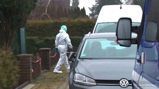 Ein Kriminalpolizist in einem weißen Overall geht vor einem Einfamilienhaus zu einem Einsatzfahrzeug am Tatort in Bergen (Archivbild).