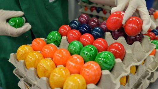 Eine Frau sortiert am 25.03.2015 in einem Betrieb in Niedersachsen bunt gefärbte Eier in Eierkartons. Das niedersächsische Landesamt für Verbraucherschutz und Lebensmittelsicherheit (Laves) hat bemalte Eier im Supermarkt untersucht.