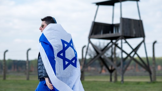 Ein Mann mit israelischer Flagge vor dem Konzentrationslager Auschwitz. Beim jährlich stattfindenden Marsch der Lebenden gedenken Juden aus Israel und anderen Ländern den Opfern der Schoah (Symbolfoto).