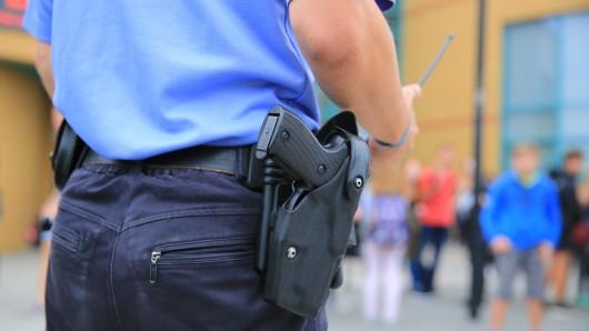 Ein Polizeibeamter steht auf dem Gelände einer Schule (Symbolbild).