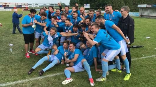 Spieler, Trainer und Betreuer von Lupo Martini feiern die Oberliga-Meisterschaft und den Wiederaufstieg in die Regionalliga.