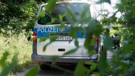 in Polizeifahrzeug steht zur Wache auf einem Feldweg, der parallel zur Bundesstraße B65 verläuft. Ein Radfahrer hatte am 27. Mai an dem Wirtschaftsweg in Höver die Leiche einer gewaltsam getöteten Frau entdeckt.