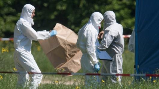 Mitarbeiter der Spurensicherung suchen in der Nähe der Fundstelle nach Hinweisen auf den Täter (Archivfoto).