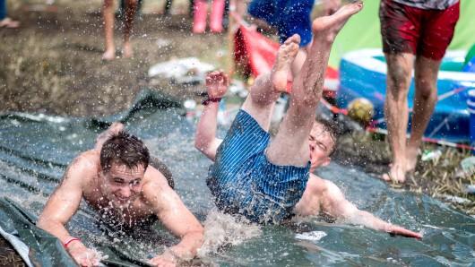 Zwei junge Männer springen auf dem Zeltplatz des Hurricane Festivals auf eine mit Wasser geflutete Rutschbahn.