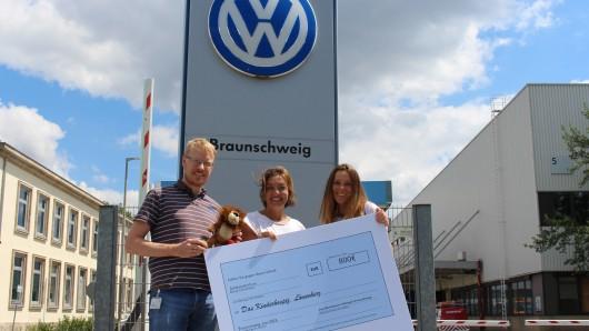 Die Volkswagen-Mitarbeiter Jan Voigt (links) und Katja Saathoff (rechts) bei der symbolischen Scheckübergabe an Isa Groth vom Kinderhospiz Löwenherz.